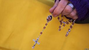 A woman in the crowd holds a small cross before the arrival of Pope Benedict XVI at his last general audience at St Peter's Square at the Vatican on 27 February 2013