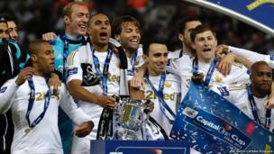 Swansea City players celebrate with the trophy after winning the English League Cup