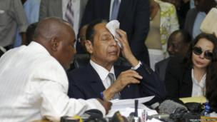 Jean Claude Duvalier wipes sweat from his brow