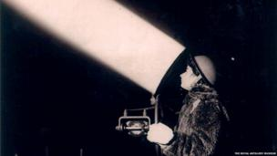 Archive photograph of a woman with searchlight at night
