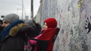 A man and baby stand in front of the Berlin Wall