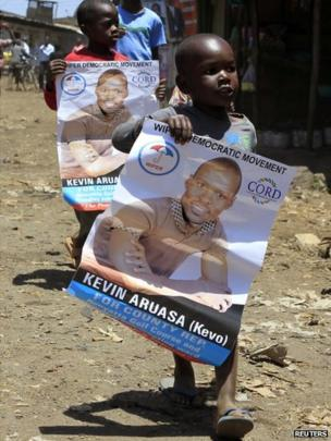 Young boys carry election campaign posters of Kevin Aruasa, a candidate tied with the Coalition for Reforms and Democracy (Cord), as they stroll in their neighbourhood in Kibera slum in the capital Nairobi February 28, 2013