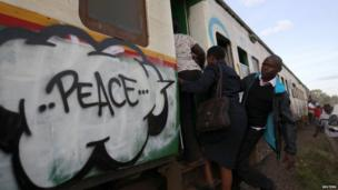 Commuters board a train painted with murals promoting peace after the coming elections in Kenya's capital Nairobi - Monday 25 February 2013