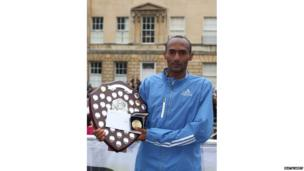 Ethiopian Tewodros Shiferaw holding his trophy and winner's medal