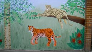 Mural of a leopard lying on the branch of a tree and a tiger on the grass below. Photo: Emma Scutt