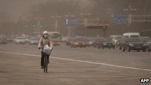 A woman cycles past traffic during a sand storm in heavily polluted weather in Beijing, 28 February 2013