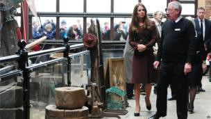 Duchess of Cambridge and John Vincent walking around National Fishing Heritage together with crowds peeking through the window in the background