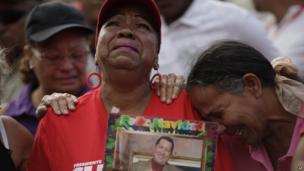 Supporters of Venezuela's President Hugo Chavez cry outside the military hospital where he died Tuesday in Caracas, Venezuela.