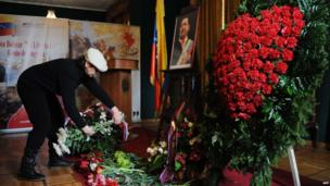 A woman lays flowers beside a picture of Hugo Chavez at the Venezuelan embassy in Moscow
