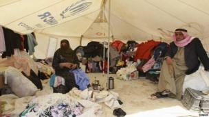 Refugees working on a second hand clothes stall in the camp
