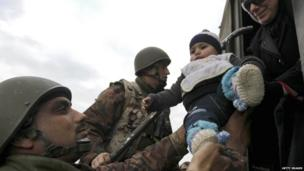 Jordanian soldiers helping refugees out of vehicle