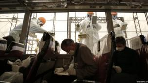 Workers carry out radiation screening on a bus