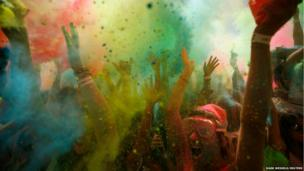 Revellers are covered in coloured cornflour powder as they take part in the Holi One festival