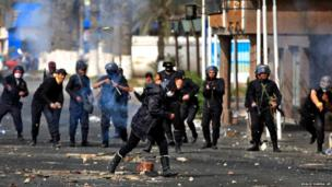 An Egyptian woman runs for cover as riot police throw stones during clashes near a state security building in Port Said, Egypt