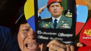 """A supporter holds a picture of the late President Hugo Chavez, reading """"We shall always remember. You shall live in our hearts"""", outside of his funeral in Caracas"""