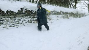 A farmer near Allenheads, Northumbria, battles through the snow to carry feed to his livestock