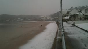 A beach and small promenade have snow on them. People walking on the beach. The sky above is grey.