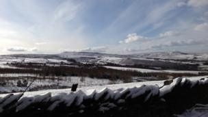 A wide view across fields covered in snow. A snow covered wall in the foreground.