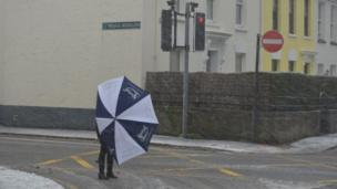 A woman with an umbrella crossing a road . The umbrella is embracing her in the strong winds. Snow is falling.