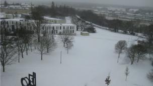 A top shot of snow-covered trees and buildings. Buses on a road. The sky is grey.