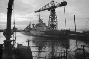 HMS Belfast moored at Rosyth, adjacent to a large crane during World War II