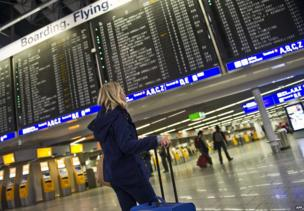 A passenger stands in front of an information board displaying flights at Frankfurt airport (12 March 2013)