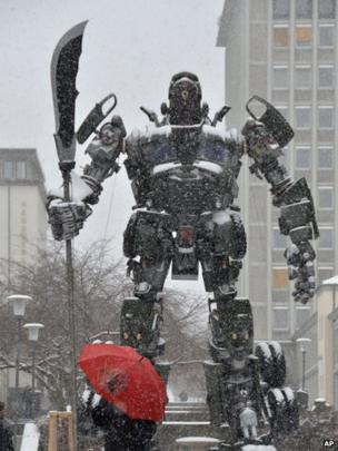 A passerby with an umbrella walks next to the sculpture Transformer by Chinese artist Bi Heng in snow in Kassel, central Germany, 12 March