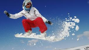 Teacher Kirsty Willett snowboards in the snow on the South Downs near Brighton in southern England