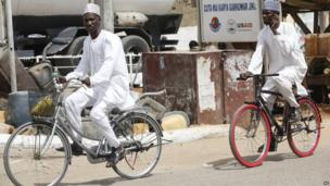 Muslim men ride on bicycles on a street in Kano, Nigeria, on 10 March 2013