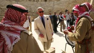 Prince Charles smiles next to members of a traditional Jordanian troupe as they welcome him during his visit to the ancient Roman ruins in Jerash