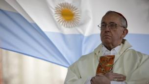 Cardinal Jorge Bergoglio gives a Mass outside the San Cayetano Church where an Argentine flag hangs behind in Buenos Aires, Argentina, in 2009