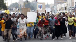 Protesters chant slogans as they celebrate after nine South African policemen accused of murder were denied bail at the Benoni court, east of Johannesburg, March 12, 2013.