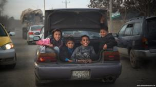 Afghan boys peer out from the boot of a car as they get a ride through the centre of Kabul