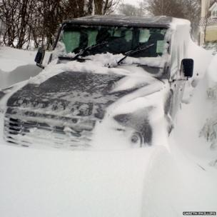 Landrover up to its window in a snow drift. Photo: Gareth Phillips