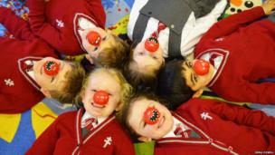 Young pupils at New Hall Preparatory School in Chelmsford lie on the floor wearing their red noses. Photo: Emma Powell