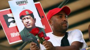 Man holds poster of Chavez. 15 March 2013