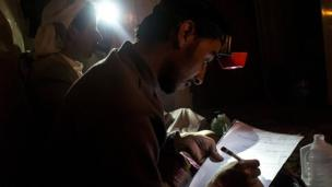 Sanaa university students work by torchlight