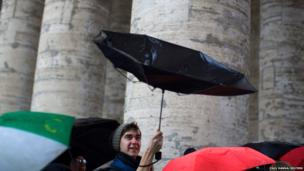 A tourist tries to hold on to his umbrella during a rainstorm in Saint Peter's Square at the Vatican