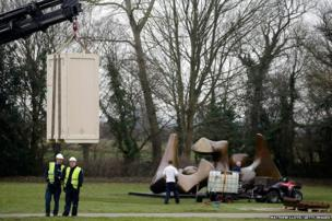 Workers unload Auguste Rodin's sculpture The Fallen Caryatid With Stone next to Henry Moore's Three Piece Sculpture - Vertebrae