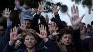 """Cypriots show their palms reading """"No"""" during a protest against an EU bailout deal outside the parliament in Nicosia on Monday"""