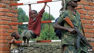 Children play near a rebel soldier in eastern DR Congo in March 2013