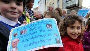Pupils of the Funtington School wave their signs as they wait for the arrival of the The Archbishop of Canterbury