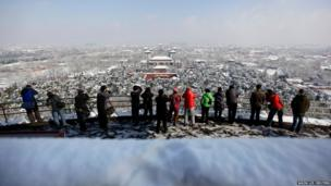 People take pictures after heavy snowfall overnight at the top of Jingshan Park in central Beijing
