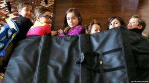Children demonstrate how they might take shelter in a school under a bulletproof blanket in Aurora