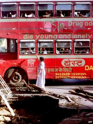 In this photograph taken on March 16, 1993, an Indian pedestrian is passed by a double-decker bus as she walks past bomb blast debris in Mumbai