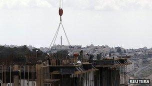The West Bank town of Bethlehem is seen in the background as Palestinian labourers work on a construction site at a Jewish settlement near Jerusalem known to Israelis as Har Homa and to Palestinians as Jabal Abu Ghneim