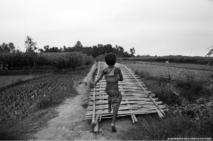 A little boy runs across a makeshift bamboo bridge.