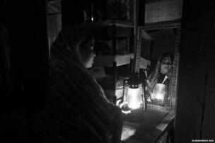 A woman lights a lantern