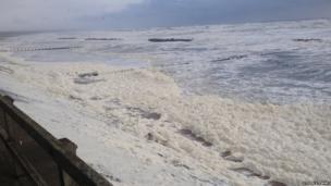 Sea foam washing on to beach front. Photo: Steven Stewart