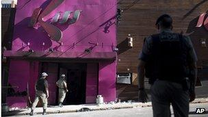 Police officers search the premises of the Kiss nightclub in January 2013